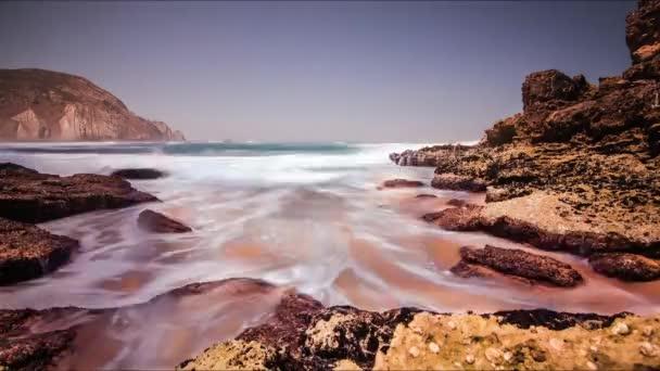 Úvodní vlny moře na skalnatém pobřeží. Pěnové vlna stříkající na kamenité pláži