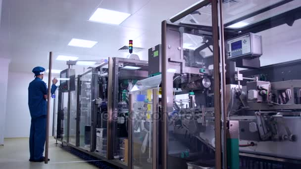 Pharmaceutical production machine. Factory worker control medical manufacturing