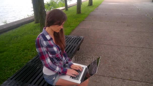 Young woman typing laptop. Girl using laptop outside. Woman with laptop outside