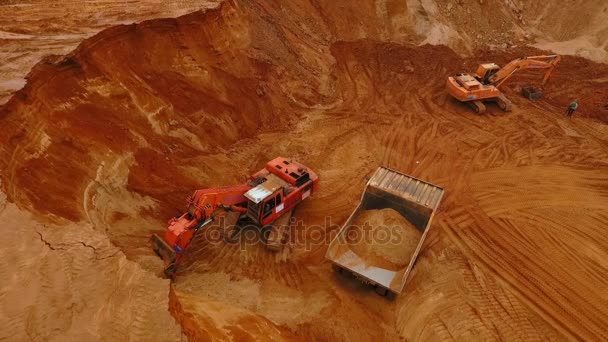 Mining machinery working at sand mine. Excavator pouring sand in mining truck
