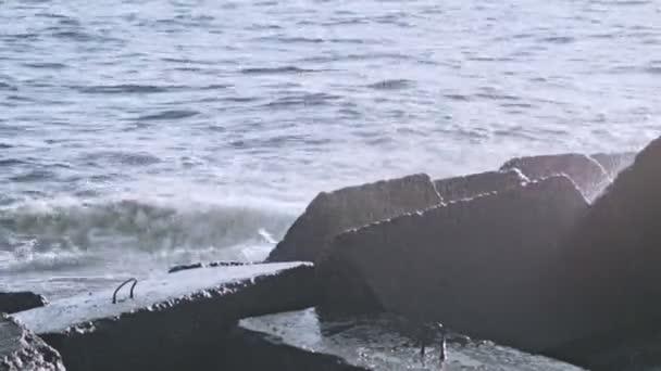 Vodní kameny. Kameny ve vodě. Vlnolamů na břehu oceánu. Burácející vlny