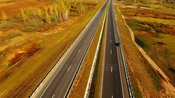 Pohled shora rovné silnici na pozadí podzimní krajiny. Podzimní les a silniční