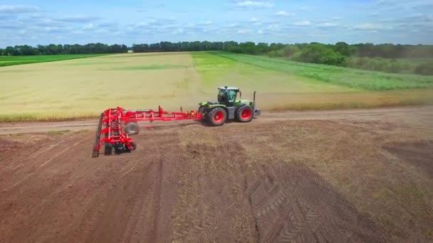 Mezőgazdasági Traktor utánfutóval szántás mezőgazdasági területen. Vidéki gazdaság