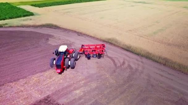 Zemědělský tahač s návěsem pro orání, pracuje na obdělávané pole