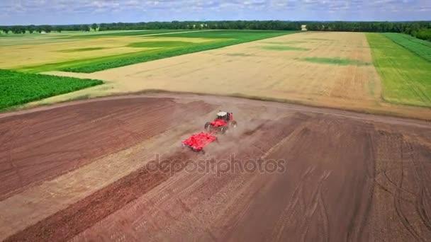 Zemědělský traktor s přívěsem orat, orání pole. Venkovské zemědělství