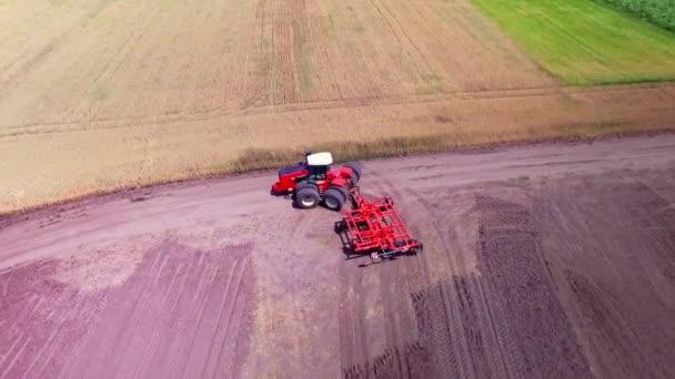 Zemědělský traktor s přívěsem orbě na zemědělské oblasti