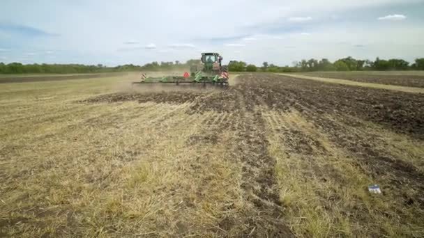 Agricultural tractor plowing field. Agricultural equipment. Plowed field