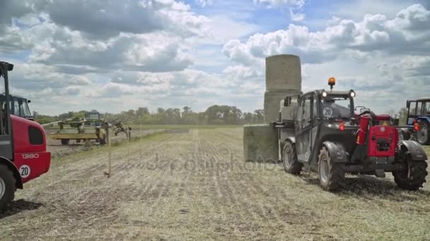 Farming tractor loading haystacks on agricultural field