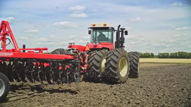 Farming tractor plowing field. Farming machinery. Agricultural machinery working