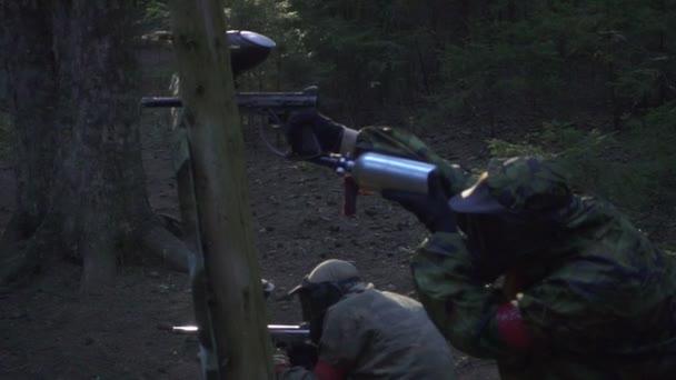 Paintball hráč střílí z pistole s splash barev na bitevním poli, v lese