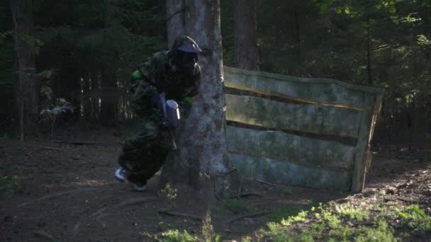Muž z hráčů ve hře paintball s pistolí běžící na střelnici v lese