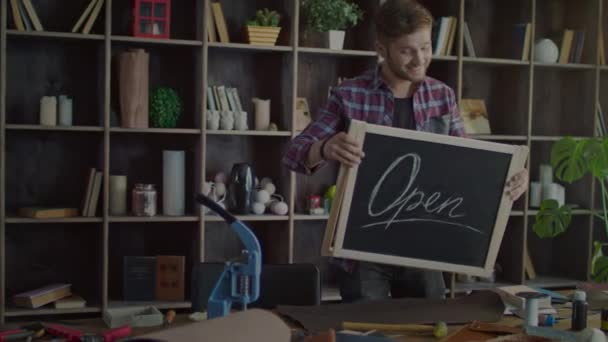 Happy business owner putting open sign on table in small shop