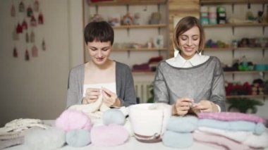 Knitting woman smiling and talking with friend sitting at table in workshop