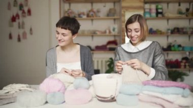 Two woman knitter talking and smiling at work table in studio