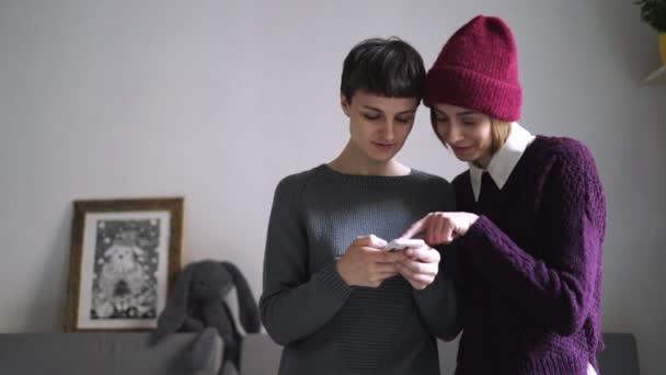Zwei junge Frau Handy Foto betrachten. Freundinnen mit Smartphone