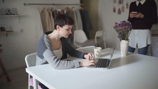Fiatal nő ül az asztalnál, és gépelés-on laptop. Nő használ szúró telefon