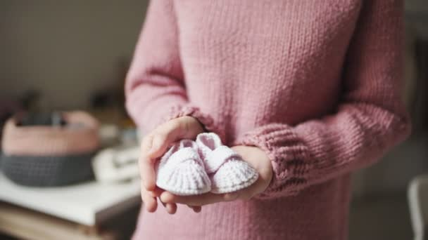 Baby booties on female palms. Knitted shoes handmade for children