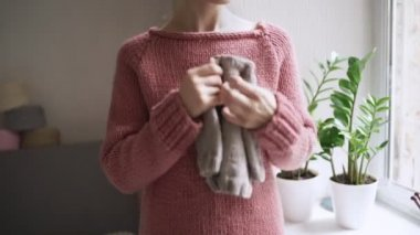 Female hands holding knitted clothes for baby. Mother expecting baby