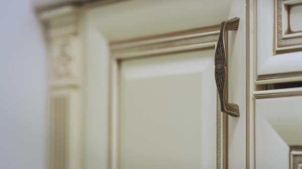 Ženská ruka otevírání dveří skříňky kuchyně a brát bílé desky na polici uvnitř
