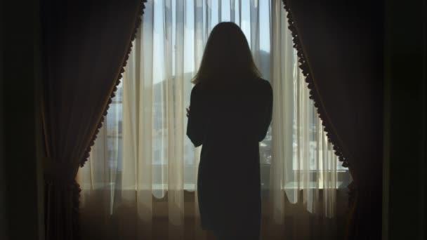 Mladá žena pěšky do okna a otevření závěsy zadní pohled