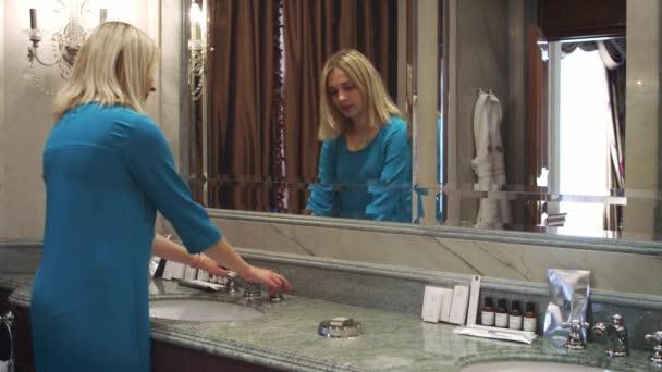 Žena obrací vodovodní kohoutek a mytí rukou v bath pokoji