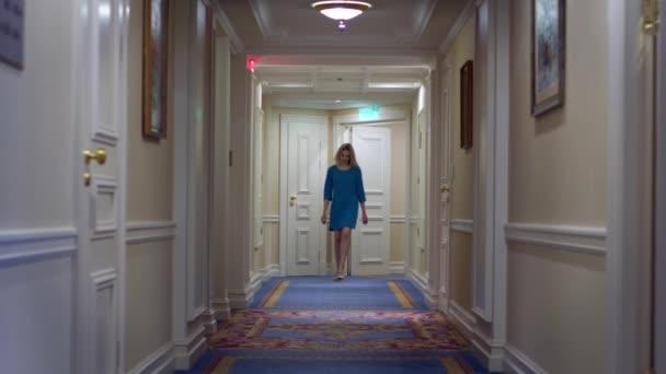 Krásná žena v modrých šatech, chůze po chodbě v luxusní rezidenci