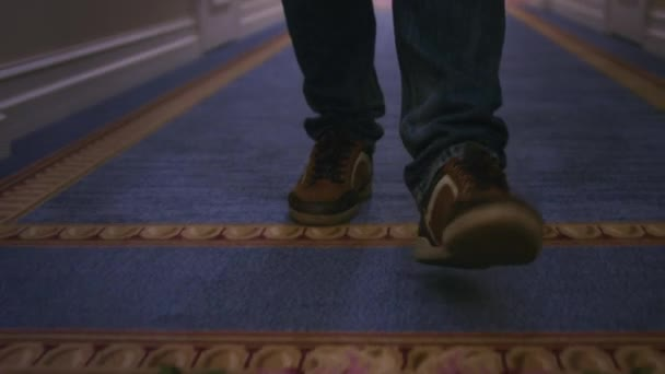 Man legs in brown sneakers walking on blue carpet on long corrido