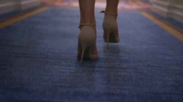 Sexy woman in beige shoes walking on carpet floor back view