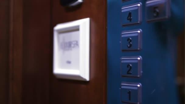 Ženská ruka tlačí třetí patro tlačítko na panelu do výtahu