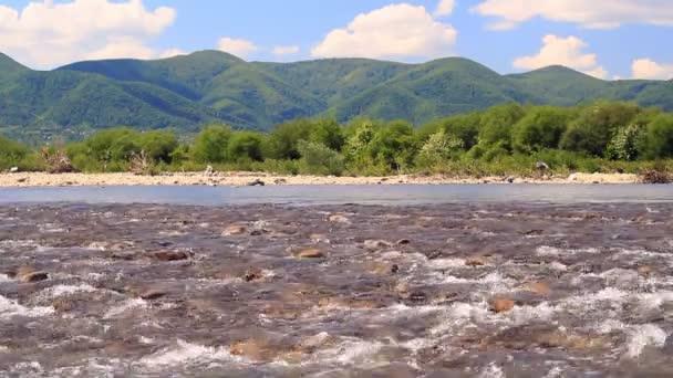 Rychlá řeka s horské panorama a kamenitých peřejí. Vodní krajina