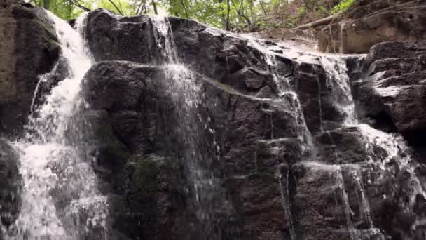 Flowing water in rocky path in natural park. Mountain waterfall stream