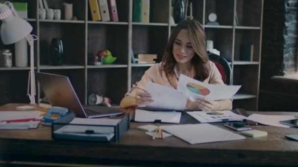 Usmíval se podnikatelka čtení dokumentů s dobré statistiky graf na stůl