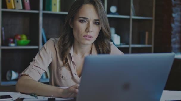 Vážná věc žena s úsměvem při práci na notebooku v úřadu