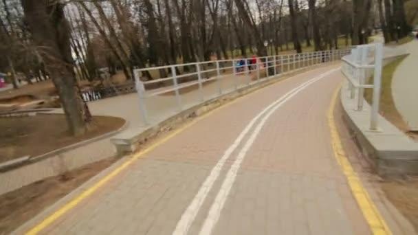 Na kole na kole po cyklostezce podél nábřeží v městském parku. Rychlost, jízda na kole