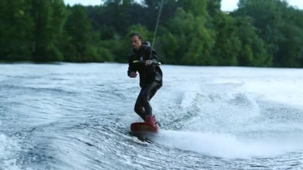 Junger Mann beim Wakeboarden auf der Flusswelle. Weckruf