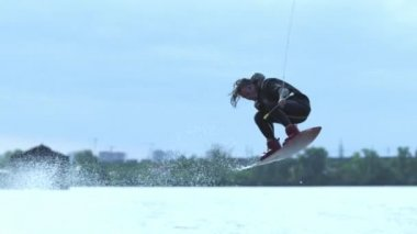 Male wakeboarder riding on river in wakeboard jumping high above water