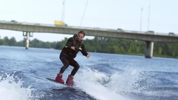 Joyful man wakeboarding on city river. Extreme entertainment on water