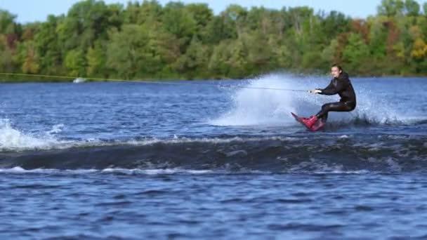 Wakeboarder skákat vysoko nad vodou. Jezdec wakeboarding