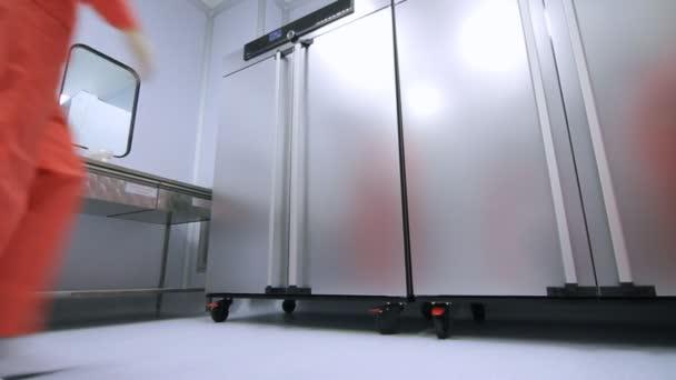 Fabrikarbeiter in orange Schutzanzug öffnen Kühlschrank Lagerung