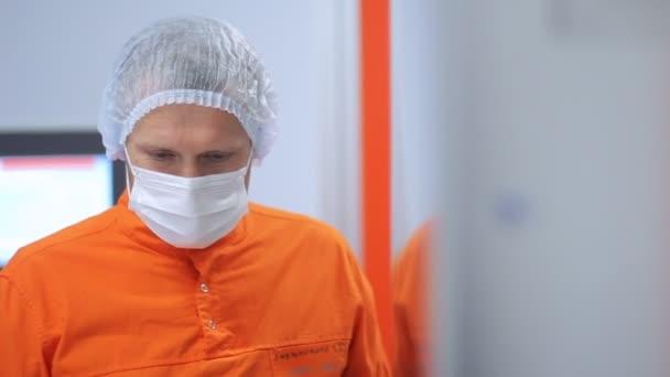 Nahaufnahme von zuversichtlich Wissenschaftler in orange Schutzanzug und Maske auf Gesicht