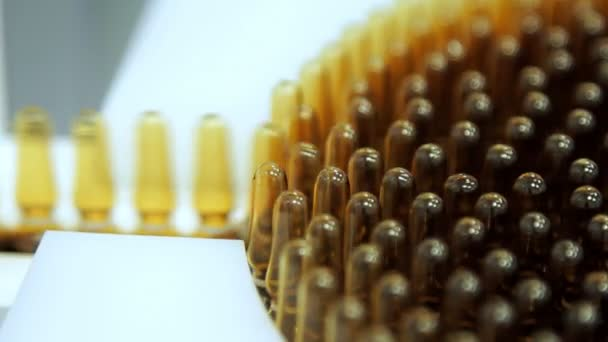 Manufacturing at pharmacy factory. Macro of medical vials on production line