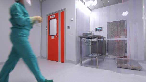 Female worker in uniform working in sterile room at pharmaceutical factory