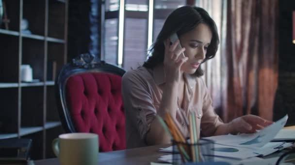 Naštvaný, podnikatelka, odpovídání na volání v mobilních při práci s dokumenty