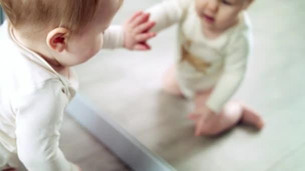 Beautiful baby looking mirror. Cute little kid looking herself. Happy childhood