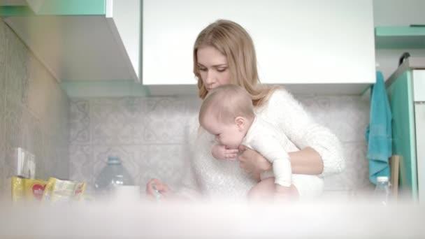 Žena s dítětem připravuje jídlo v kuchyni. Máma vaří ovesné vločky pro malé dítě
