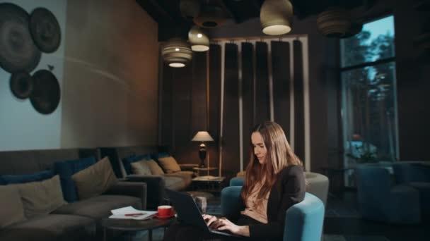 Usmívající se žena používající notebook v hotelu. Obchodní žena pracující notebook