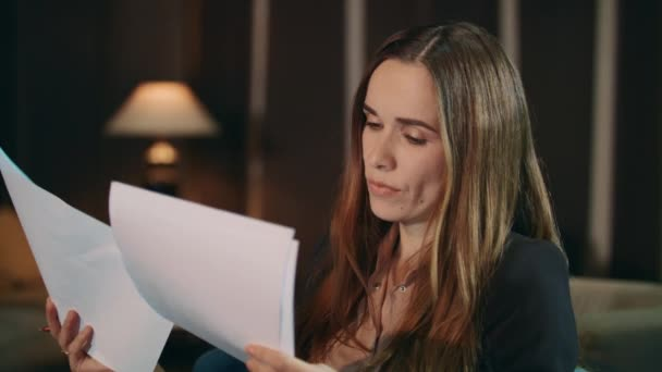 Focused woman reading financial report in office. Pensive businesswoman