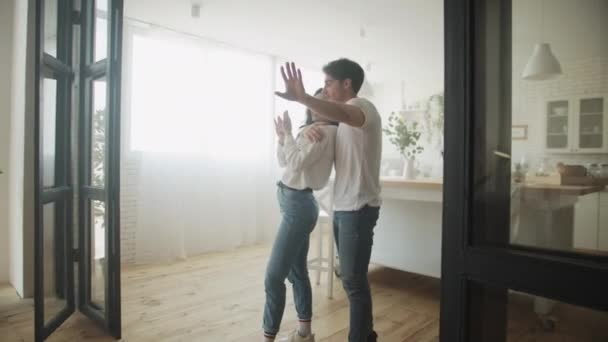 Happy homeowners planning interior design in new kitchen. Family hugging at home