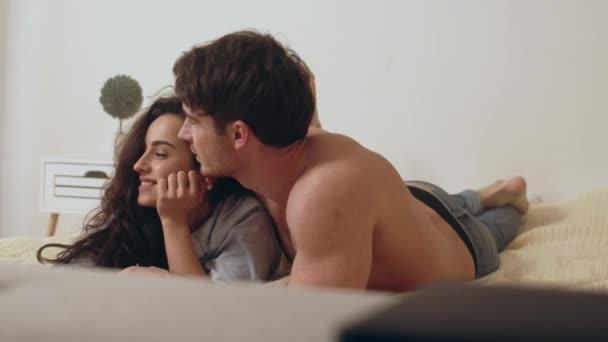 Makro eines glücklichen Paares, das im Schlafzimmer liegt. Entspannter Mann berührt Frau.