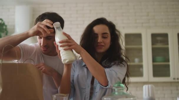 Fiatal pár flörtöl az otthoni konyhában. Boldog család, jól érzik magukat otthon.